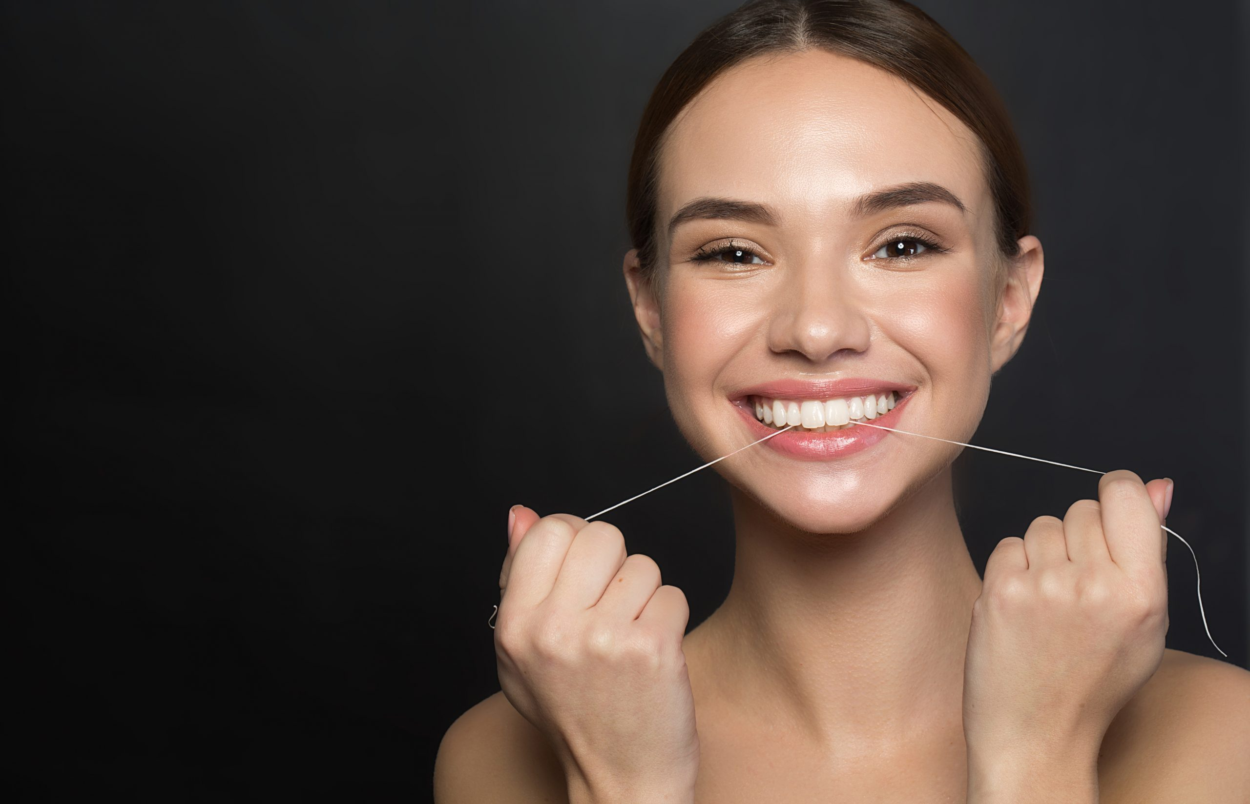 Portrait of positive young woman who is taking care of her teeth. She is holding dental floss and laughing while looking at camera with joy. Isolated and copy space in left side. Dental health concept