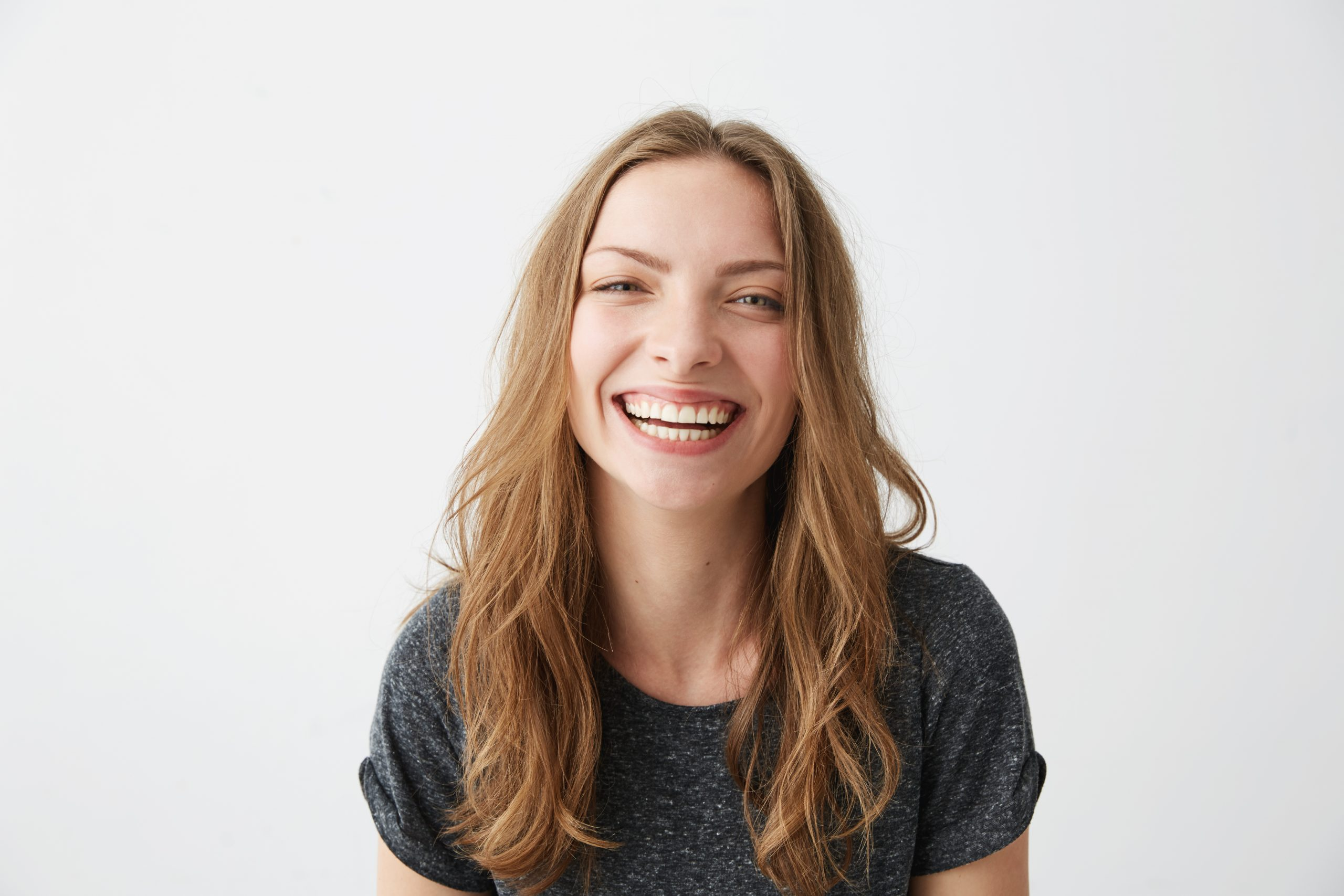 Young cheerful happy girl smiling laughing looking at camera over white background. Copy space.