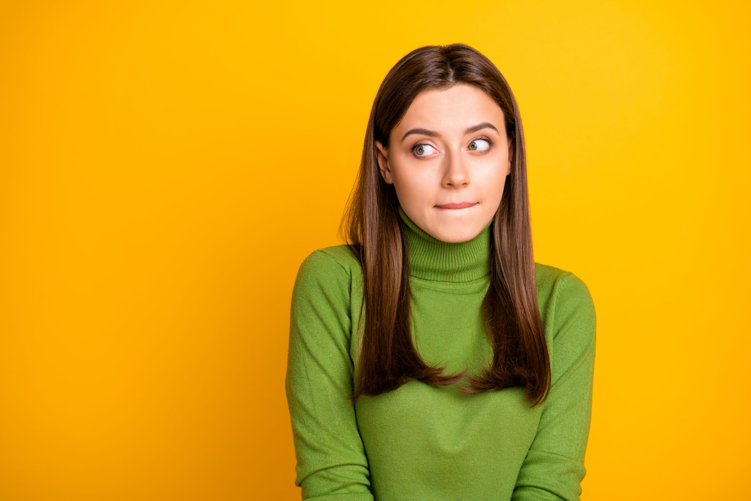 Portrait of scared frightened girl made mistake look copyspace, bite lisp wear stylish clothing isolated over bright color background